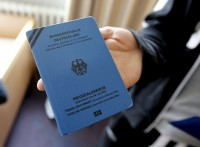 An unidentified asylum seeker from the Syrian town of Rakka displays his refugee travel document, which is also called a 1951 Convention travel document or Geneva passport, issued by the German authorities, in a refugee camp in Berlin, Germany September 21, 2015.   REUTERS/Fabrizio Bensch - RTX1RQZT